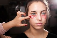 Artista de maquillaje que aplica remiendos del ojo del hidrogel en una mujer Fotografía de archivo libre de regalías
