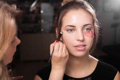 Artista de maquillaje que aplica un componer en una muchacha con el remiendo del ojo Imagen de archivo