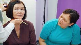 Artista de maquillaje que aprende a la mujer mayor al uso del maquillaje en escuela de la belleza metrajes