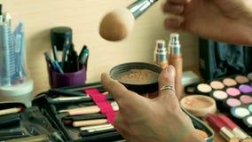 Artista de maquillaje que arregla cepillos del cosmético en un sistema grande del profesional almacen de metraje de vídeo