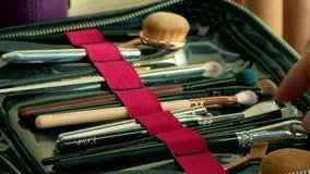 Artista de maquillaje que arregla cepillos del cosmético en un sistema grande del profesional metrajes