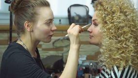 Artista de maquillaje que crea el maquillaje hermoso para el modelo rubio metrajes