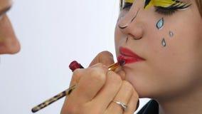 Artista de maquillaje que hace maquillaje cómico profesional del arte pop Maquillaje de la historieta divertida o de la historiet almacen de metraje de vídeo