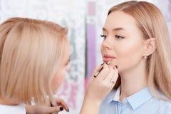 Artista de maquillaje que hace el maquillaje de labios imágenes de archivo libres de regalías