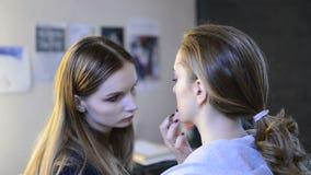 Artista de maquillaje que hace el maquillaje para el modelo antes de la sesión de foto metrajes