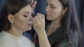 Artista de maquillaje que hace el maquillaje para el modelo antes de la sesión de foto almacen de metraje de vídeo