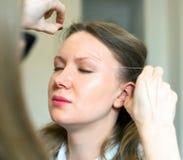Artista de maquillaje que hace la corrección de la ceja foto de archivo