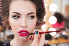 Artista de maquillaje que hace maquillaje y que aplica el lápiz labial rosado usando cepillo foto de archivo