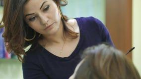 Artista de maquillaje que hace un maquillaje modelo del ` s en el salón almacen de video