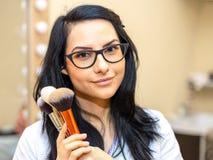 Artista de maquillaje que sostiene cepillos makeover Piel perfecta imagen de archivo libre de regalías