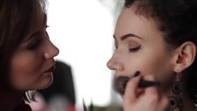 Artista de maquillaje que trabaja con el modelo metrajes