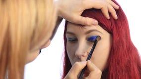 Artista de maquillaje que trabaja con un modelo de la persona Opinión del primer de una mano del ` s del artista usando cepillo e metrajes
