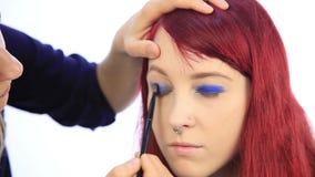 Artista de maquillaje que trabaja con un modelo de la persona Opinión del primer de una mano del ` s del artista usando cepillo e almacen de video