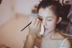 Artista de maquillaje que trabaja en modelo asi?tico hermoso fotografía de archivo
