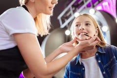 Artista de maquillaje que usa el cepillo para aplicar el lápiz labial a los labios de las muchachas Fotos de archivo libres de regalías