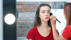Artista de maquillaje de sexo femenino profesional que trabaja con la mujer bastante europea de los jóvenes que usa el cepillo metrajes