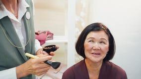 Artista de maquillaje usando el cepillo cosmético para que cara del maquillaje madure a la mujer en estudio almacen de metraje de vídeo