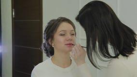 Artista de maquillaje usando el cepillo para la barra de labios del uso en mujer hermosa de los labios Cierre encima del lustre d metrajes