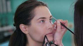Artista de maquillaje y peluquero que trabajan con el cliente en la tienda de belleza almacen de video