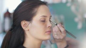Artista de maquillaje y peluquero que trabajan con el cliente en la tienda de belleza almacen de metraje de vídeo