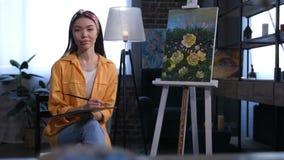 Artista de sexo femenino asiático atractivo que se sienta cerca de lona metrajes