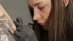 Artista de sexo femenino caucásico del tatuaje en vías del trabajo, mediados de opinión sobre cara enfocada almacen de video