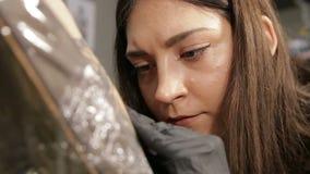 Artista de sexo femenino caucásico del tatuaje en vías del trabajo, opinión del primer sobre cara enfocada almacen de metraje de vídeo