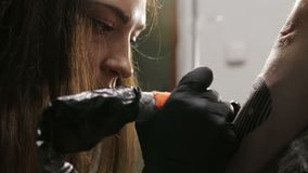 Artista de sexo femenino caucásico hermoso del tatuaje centrado en proceso de su trabajo metrajes