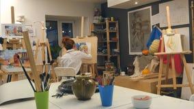 Artista de sexo femenino del jengibre todavía que pinta vida en estudio del arte Foto de archivo libre de regalías