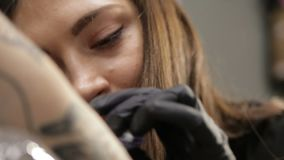 Artista de sexo femenino del tatuaje en vías del trabajo, opinión del primer sobre cara almacen de metraje de vídeo