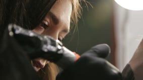 Artista de sexo femenino del tatuaje que habla con su cliente durante el proceso del tatuaje almacen de metraje de vídeo