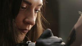 Artista de sexo femenino del tatuaje que habla con su cliente durante el proceso del tatuaje metrajes