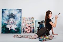 Artista de sexo femenino en la lona de la imagen en el fondo blanco Pintor de la muchacha con los cepillos y la paleta Concepto d foto de archivo