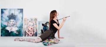 Artista de sexo femenino en la lona de la imagen en el fondo blanco Pintor de la muchacha con los cepillos y la paleta Concepto d Imágenes de archivo libres de regalías