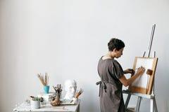 Artista de sexo femenino en su estudio blanco espacioso Imagen de archivo libre de regalías