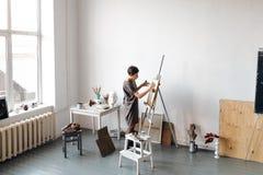 Artista de sexo femenino en su estudio blanco espacioso Imágenes de archivo libres de regalías