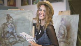 Artista de sexo femenino feliz antes de caballetes almacen de metraje de vídeo