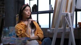 Artista de sexo femenino inspirado que piensa en su pintura almacen de video