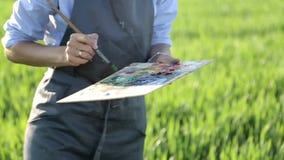 Artista de sexo femenino joven en las pinturas que pintan pinturas en una lona en un campo verde almacen de metraje de vídeo