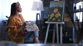 Artista de sexo femenino joven que admira su pintura acabada almacen de metraje de vídeo