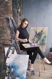 Artista de sexo femenino joven que pinta la imagen abstracta en el estudio, retrato atractivo hermoso de la mujer imagen de archivo