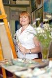 Artista de sexo femenino que pinta una imagen Fotos de archivo libres de regalías