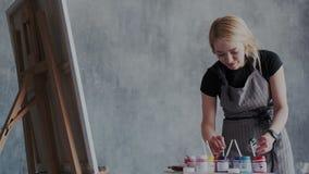 Artista de sexo femenino rubio feliz en hacer de los apronis qué ella tiene gusto Ella se coloca delante del caballete y de la pi almacen de video