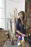 Artista de sexo femenino Sitting In Art Studio Fotografía de archivo