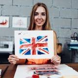 Artista de sexo femenino sonriente que le muestra los trabajos, bandera británica dibujada con técnica de la acuarela foto de archivo