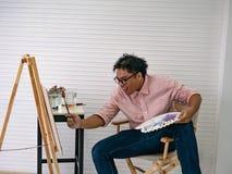 Artista de sexo masculino adulto joven Feeding de la acuarela los pescados mientras que dibuja la pintura de los pescados, imagenes de archivo