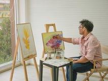 Artista de sexo masculino adulto joven Feeding de la acuarela los pescados mientras que dibuja la pintura de los pescados, fotos de archivo libres de regalías