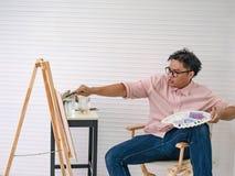Artista de sexo masculino adulto joven Feeding de la acuarela los pescados mientras que dibuja la pintura de los pescados, fotografía de archivo