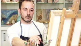 Artista de sexo masculino maduro que trabaja en una pintura en su estudio del arte