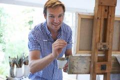 Artista de sexo masculino Painting In Studio Imágenes de archivo libres de regalías